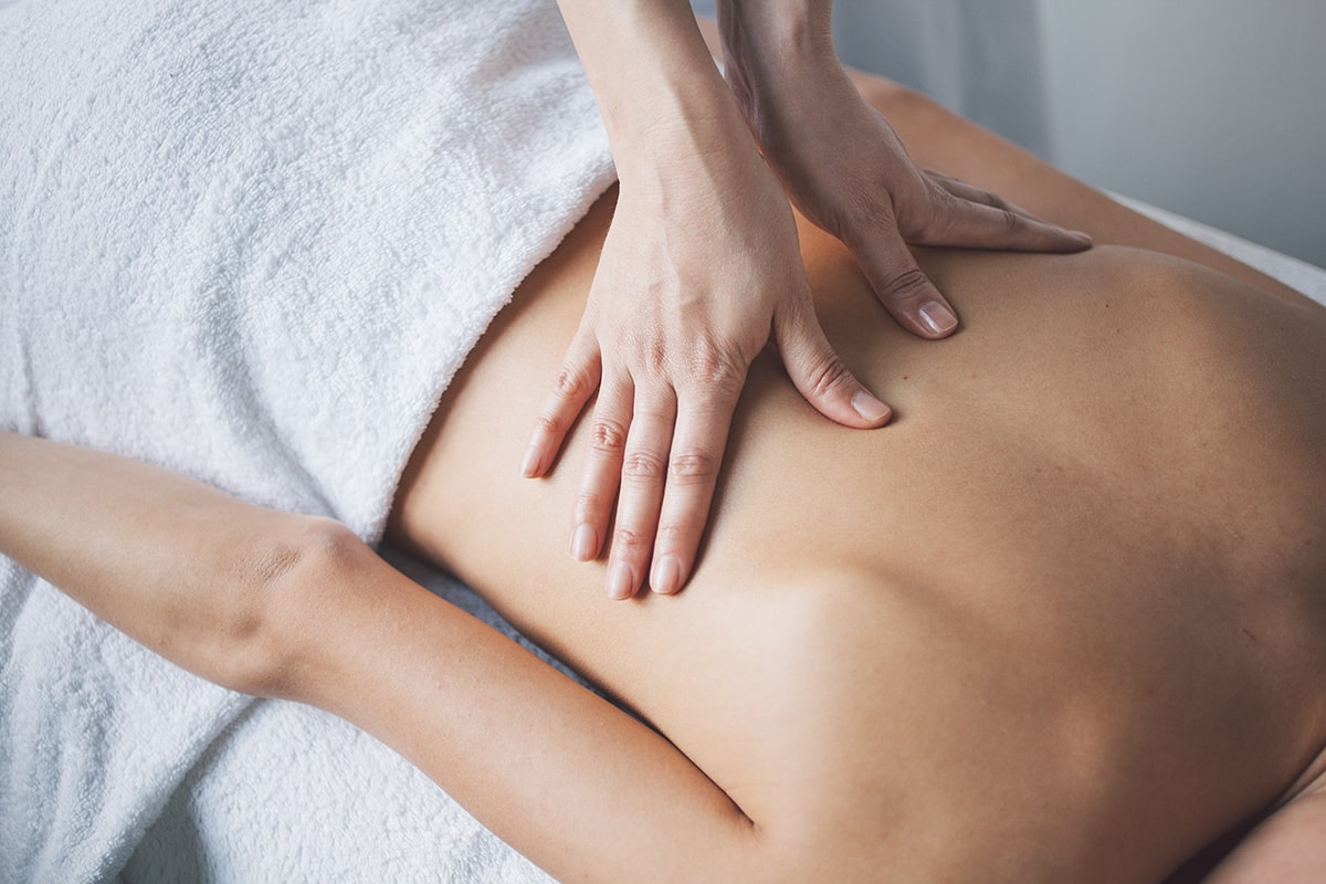 Woman getting back massage to alleviate stress in rehab